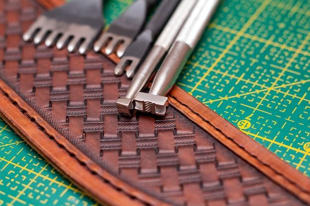 Fazendo estampagem em couro com ferramentas artesanais de couro close-up