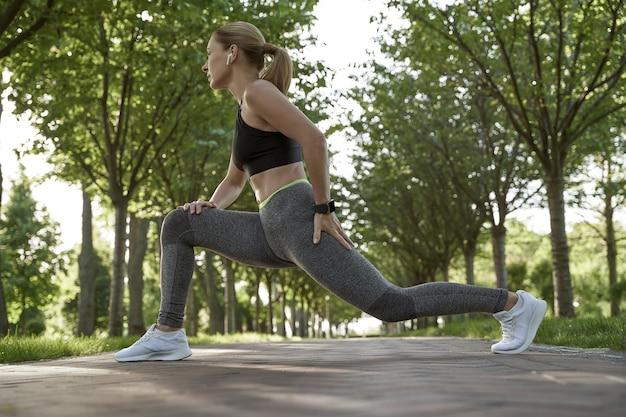 Fazendo exercícios de alongamento em uma mulher bonita fitness em roupas esportivas, esticando as pernas