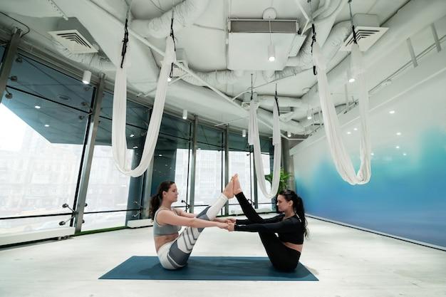 Fazendo exercícios de prancha. mulheres de cabelos escuros, magras e em forma, sentadas em tapetes esportivos fazendo exercícios de prancha