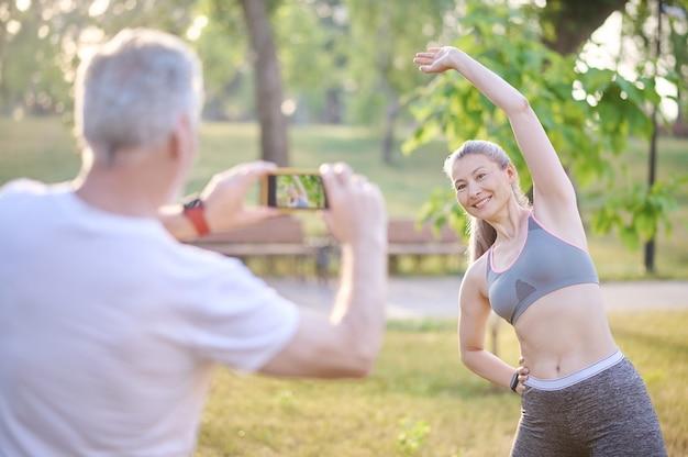 Fazendo fotos. um homem fazendo uma foto de sua esposa enquanto ela se exercitava