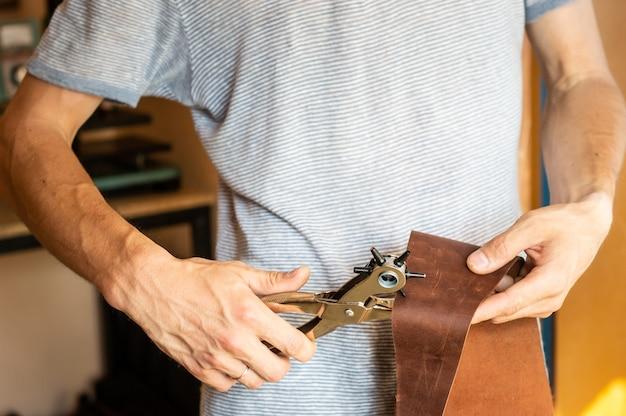 Fazendo furos com perfurador na oficina de couro. mãos masculinas com perfurador de ilhó trabalhando com pedaço de material