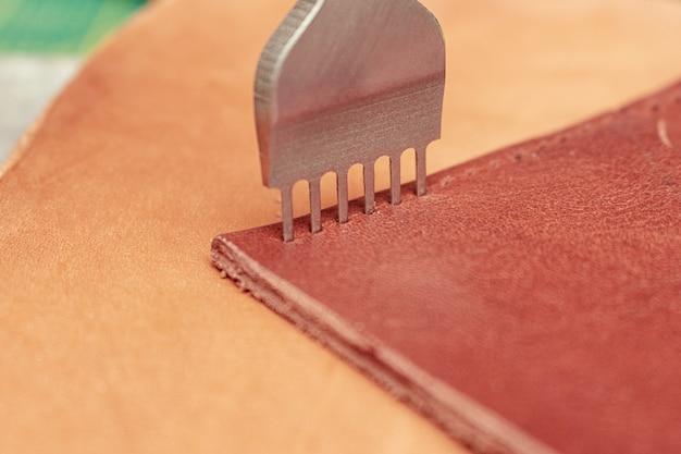 Fazendo furos em couro com a ferramenta perfurador. carteira de costura.