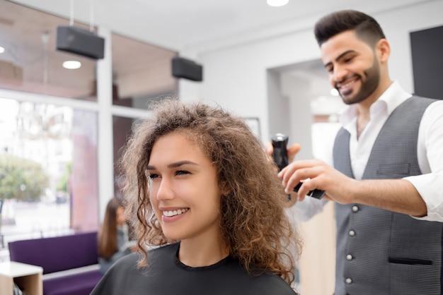 Fazendo hairdress para cliente feminino encaracolado sorridente.