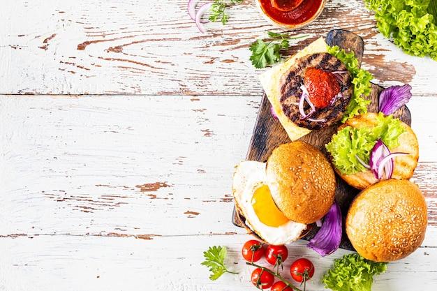 Fazendo hambúrguer caseiro. ingredientes para cozinhar em uma mesa de madeira. vista superior ou plana leiga. copie o espaço