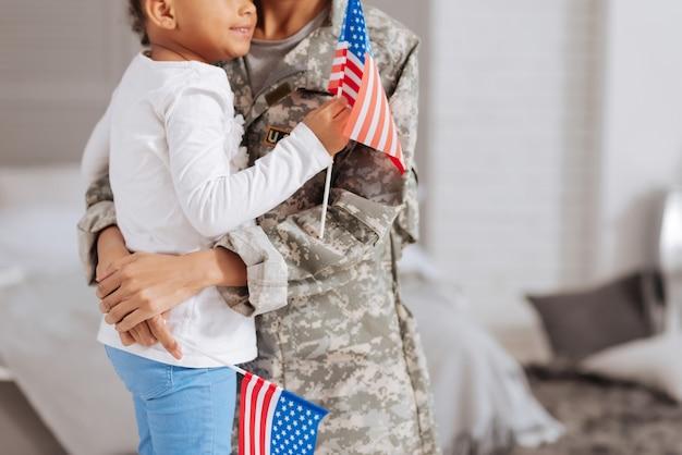 Fazendo isso pelo meu condado. impressionante e apaixonada mãe e filha segurando bandeiras nas mãos enquanto ficam perto e se abraçando