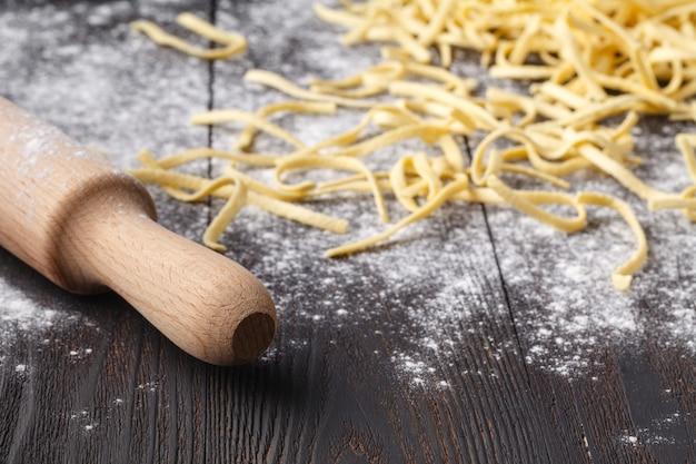 Fazendo linguine de massas caseiras na mesa da cozinha rústica com farinha, peneira vintage e tábua