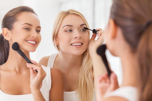 Fazendo maquiagem juntos. duas lindas mulheres fazendo maquiagem juntas enquanto se olham no espelho e sorriem