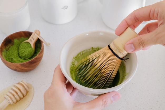 Fazendo matcha chá verde com leite, bebidas na moda saudáveis