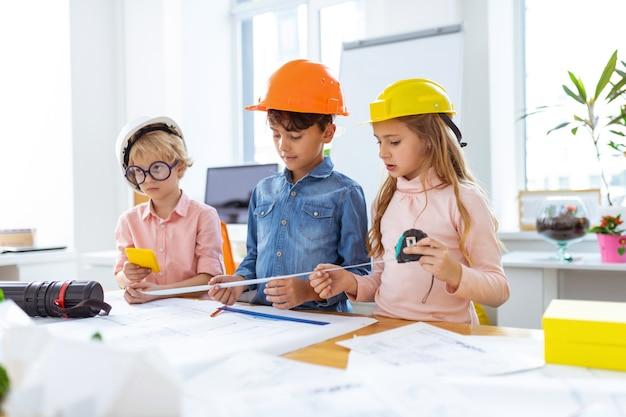 Fazendo medições. três alunos inteligentes fazendo medições enquanto fazem esboços de construção