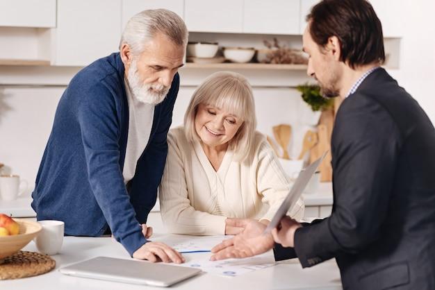 Fazendo meu trabalho corretamente. habilidoso otimista sincero corretor imobiliário, conversando com clientes idosos e usando documentos importantes enquanto representa a casa