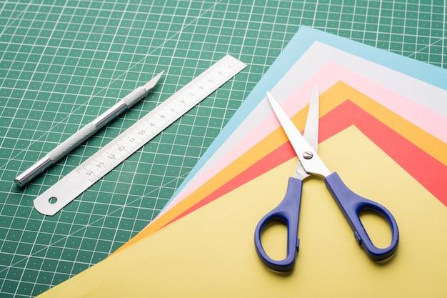 Fazendo modelos diferentes com papel. arte-final com papéis. tesoura, bisturi, pilha de papéis e régua na esteira de corte