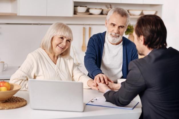 Fazendo negócio de sucesso. casal de idosos satisfeito e sorridente, sentado em casa, fechando um acordo com o agente imobiliário enquanto apertava as mãos e expressava felicidade