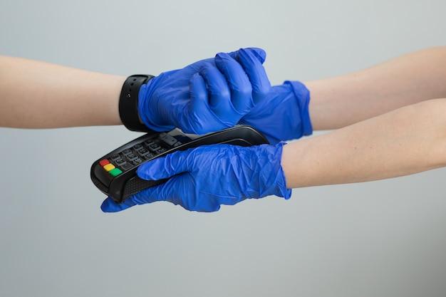 Fazendo o pagamento com relógio inteligente e terminal pos. cliente que paga com tecnologia nfc pelo relógio inteligente sem contato no terminal.