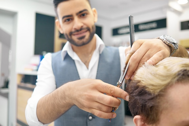 Fazendo o penteado novo para o modelo masculino usando tesouras metálicas afiadas.