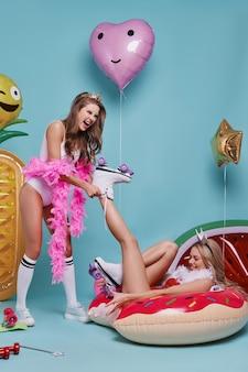 Fazendo o que quiserem. mulher jovem e bonita removendo o patim do pé do amigo e sorrindo enquanto posava contra um fundo azul