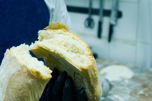 Fazendo pão ciabatta na padaria. um cozinheiro de luvas quebra o pão em duas metades