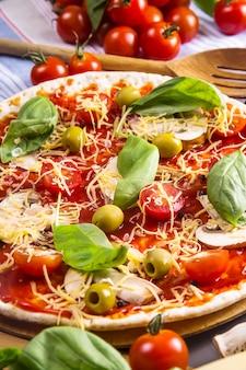 Fazendo pizza caseira de massa com cogumelos, tomate e queijo