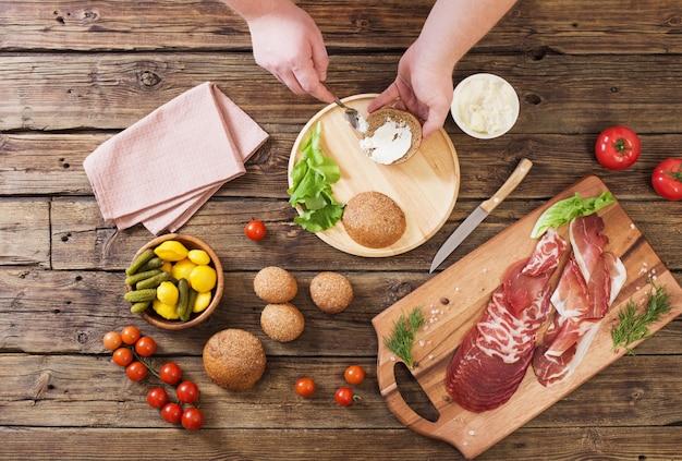 Fazendo sanduíches com carne e linguiça na mesa de madeira
