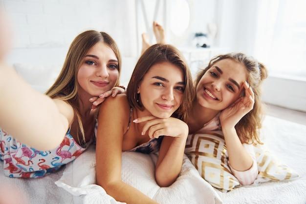 Fazendo selfie. felizes amigas se divertindo na festa do pijama no quarto.