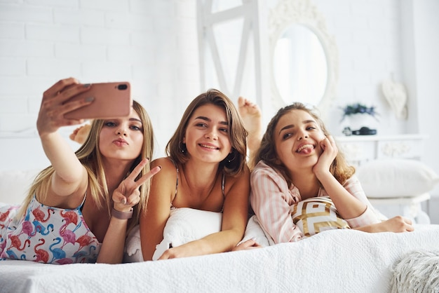 Fazendo selfie usando o telefone rosa. felizes amigas se divertindo na festa do pijama no quarto.