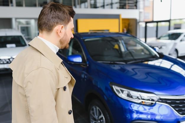 Fazendo sua escolha. retrato horizontal de um jovem de terno olhando para o carro e pensando se deveria comprá-lo