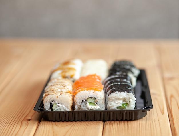 Fazendo sushi e pãezinhos em casa. sushi com frutos do mar, salada e arroz branco. comida para família e amigos. um conjunto de diferentes rolos e sushi em uma bandeja.