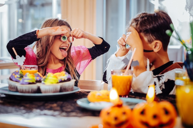 Fazendo truques. irmão e irmã fofos e engraçados sentindo-se incrivelmente felizes pregando peças na festa de halloween
