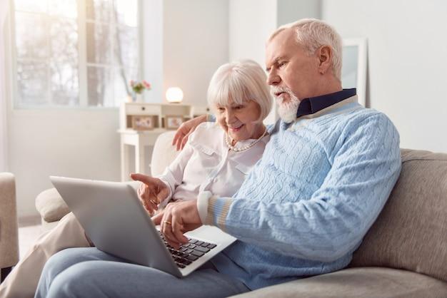 Fazendo tudo juntos. casal de idosos alegres, sentado no sofá da sala de estar, escolhendo algo em uma loja online enquanto faz compras online