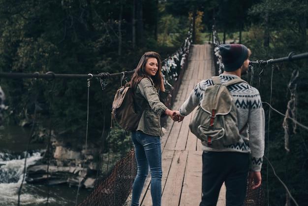 Fazendo um ao outro feliz. jovem casal sorridente de mãos dadas enquanto caminha na ponte pênsil
