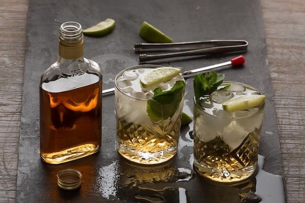 Fazendo um coquetel alcoólico com rum, gelo e limão