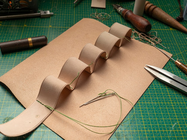 Fazendo um estojo de couro para baterias por um curtidor, em um tapete verde auto-cicatrizante, conceito de artesanato em couro