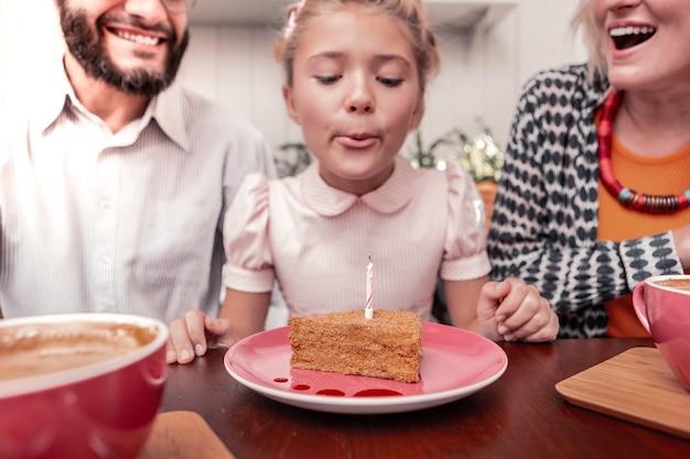 Fazendo um pedido. foco seletivo de um pedaço de bolo com uma vela enquanto é soprado em