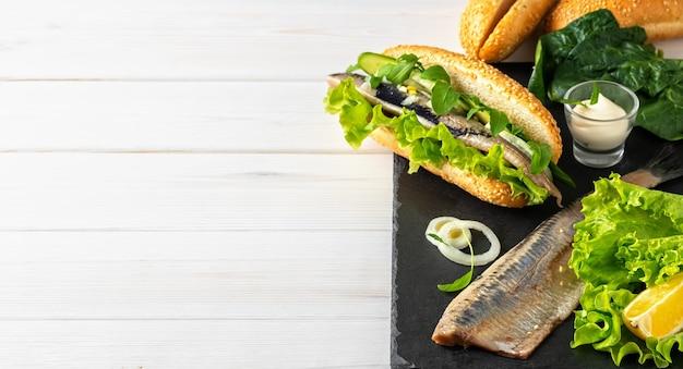 Fazendo um sanduíche de filé de arenque com cebola, pepino e salada em uma tábua de pedra