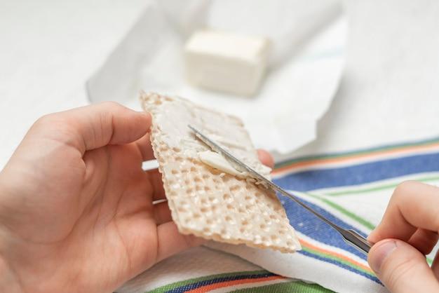Fazendo um sanduíche matinal com manteiga e pão, lanche rápido um