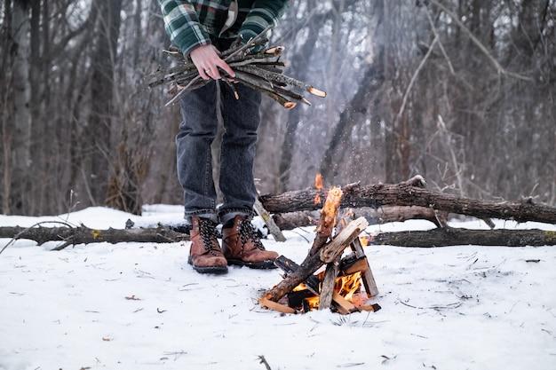 Fazendo uma fogueira em uma floresta de neve. indivíduo do sexo masculino perto de um incêndio em um dia de inverno na floresta