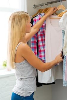 Fazendo uma importante escolha de estilo. vista lateral de uma jovem escolhendo roupas