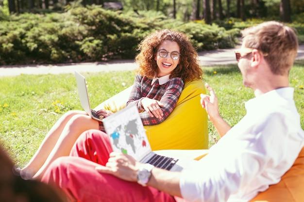 Fazendo uma pausa. exuberante garota de cabelos encaracolados trabalhando em seu laptop e seu colega sentado nela