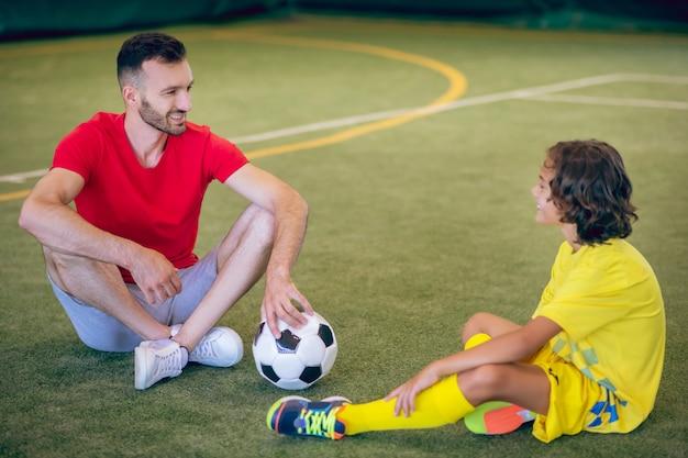 Fazendo uma pausa. menino de uniforme amarelo e seu treinador fazendo uma pausa após o jogo