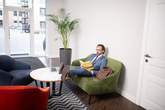 Fazendo uma pequena pausa. homem de negócios grisalho de óculos lendo o livro enquanto faz uma pausa