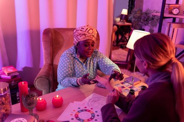 Fazendo uma previsão. cartomante rechonchudo afro-americano usando um anel enorme fazendo uma previsão