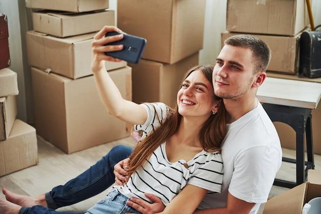 Fazendo uma selfie. casal jovem alegre em seu novo apartamento. concepção de movimento.
