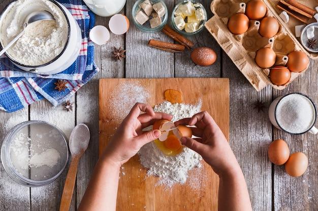 Fazendo vista superior da massa. sobrecarga das mãos do padeiro quebrar ovo na farinha. cozinhar ingredientes para pastelaria em madeira rústica, aulas de culinária ou conceito de receita.