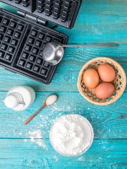 Fazendo waffles em casa - waffles, massa na tigela e ingredientes - leite, ovos e farinha.