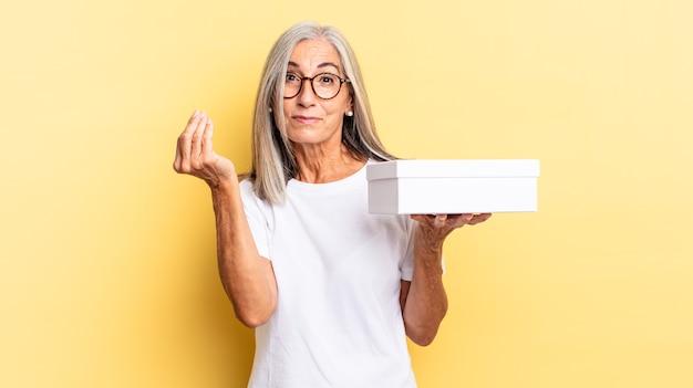 Fazer capice ou gesto de dinheiro, mandando você pagar suas dívidas! e segurando uma caixa branca