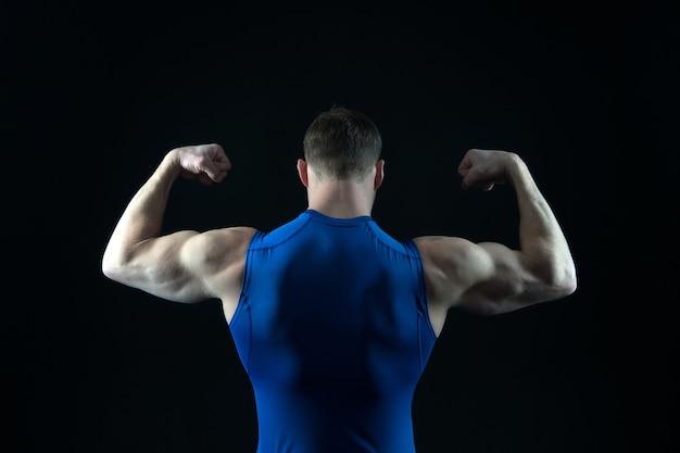 Fazer dieta e fitness fisiculturista atlético pose isolada em um fundo preto homem com corpo musculoso