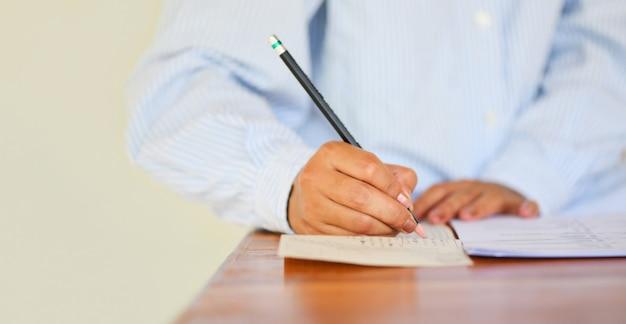 Fazer exame, a, exame final, escola secundária, estudante universitário, segurando, lápis, escrita, ligado, papel, folha resposta