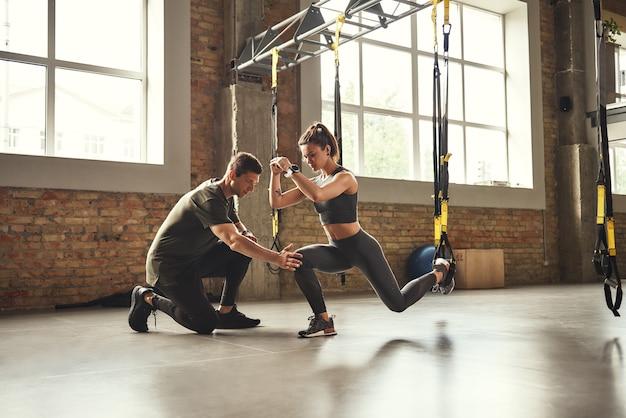 Fazer exercícios de agachamento, jovem personal trainer confiante, está mostrando a uma mulher atlética magra como fazer