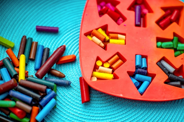 Fazer lápis de cera caseiros a partir dos destroços de giz de cera velho, derretendo-os no forno a alta temperatura em forma de silicone. corte de vida
