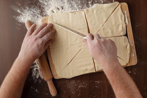 Fazer massa por mens mãos na mesa de madeira