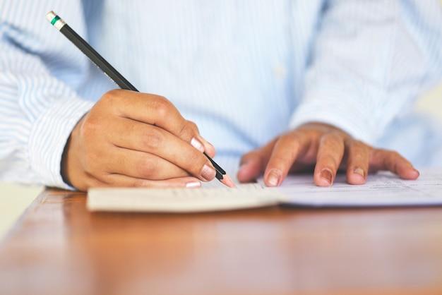 Fazer o exame final do estudante universitário segurando o lápis escrevendo na folha de respostas em papel